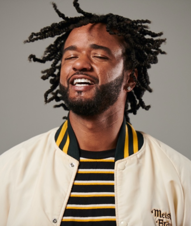 Professional Barber and Stylist Community Man with dreads and white jacket