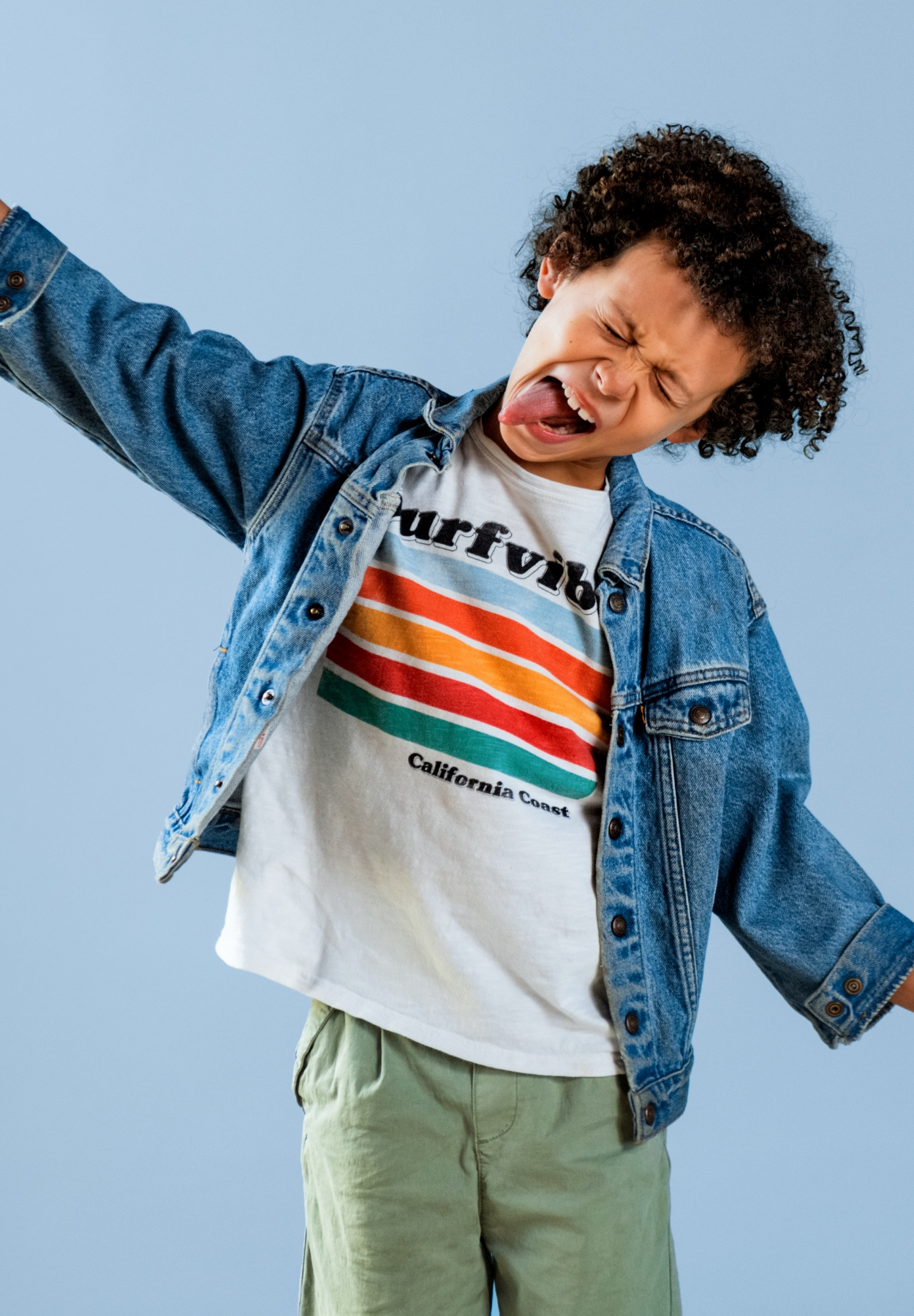 Boy with curly brown hair making face wearing jean jacket